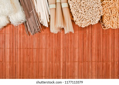 Different bundles of uncooked asian noodles (udon, soba, ramen, rice and glass noodles) close up on bamboo background. Top view. Text space.