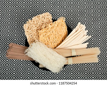 Different bundles of uncooked asian noodles (udon, soba, ramen, rice and glass noodles) in black clay bowl on patterned textile background. Top view.