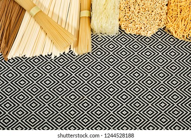 Different bundles of uncooked asian noodles (udon, soba, ramen, rice and glass noodles) on patterned textile background. Top view.