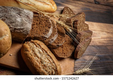 Different buns of fresh bread and spikelets of wheat on a brown vintage background