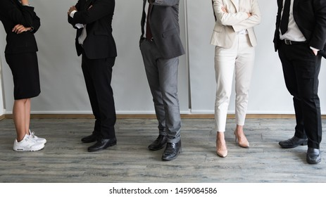 Different business people standing in row, close up at legs.