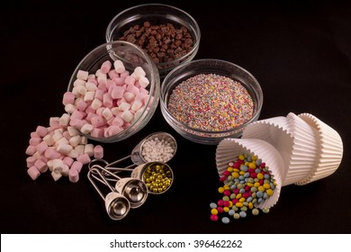 Different cake decorations laid out against a black background