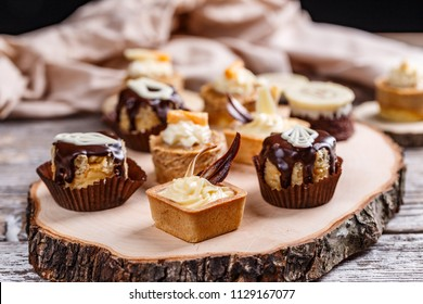 Different cakes standing on a wooden board