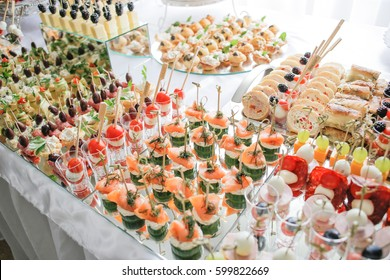 Different canapes with smoked salmon, cucumber cherry tomatoes and mozzarella served on a table