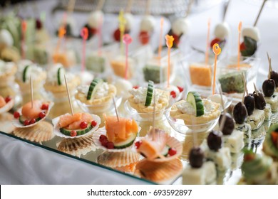 Different canapes with smoked salmon, cucumber and red currant served on sea shell over a mirror plate. Pastry cream cheese and cucumber canapes. Gorgonzola and olives Small catering canape.