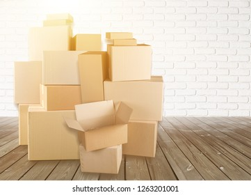 Different cardboard boxes in room on wooden floor