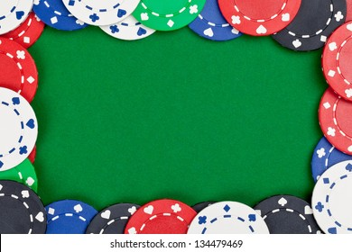 Different casino chips frame on green table background with copyspace