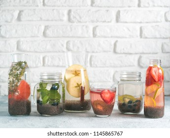 Different chia water in glass on gray background. Chia infused detox water with berries, fruits and herbs. Healthy eating, drinks, diet, detox concept. Copy space for text