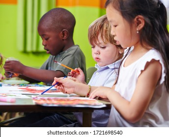 Different children concentrate together painting pictures in kindergarten