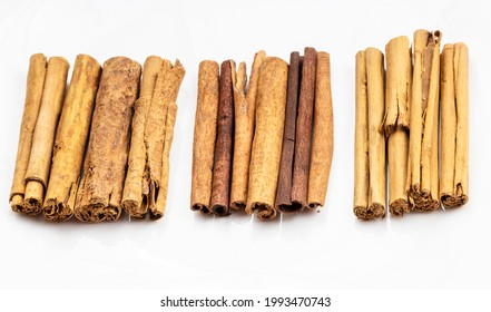 different cinnamon sticks (alba premium ceylon, chinese cassia and continental ceylon cinnamon) on white plate