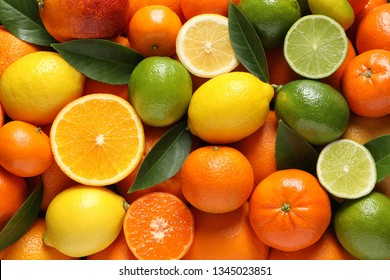 Different citrus fruits with leaves as background, top view