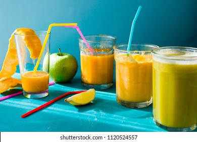 Different citrus juce poured and drunk on jar glass with colored straws on a blu aqua background, summertime concept and healthy lifestyle.