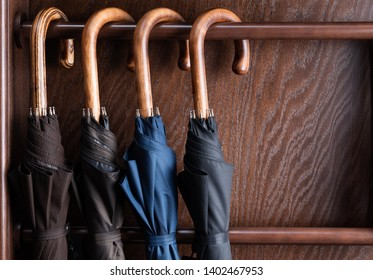 Different classic wooden handle walking length umbrellas on display in luxury clothing boutique store.