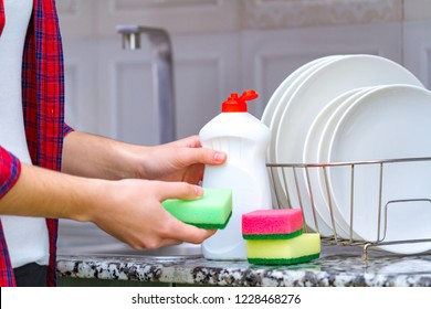 Different clean plates in dish drying rack, dish sponges and dishwashing detergent on the table on kitchen counter.