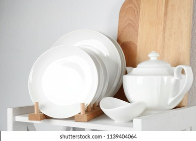 Different clean tableware on shelf in kitchen