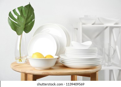 Different clean tableware on wooden table in kitchen