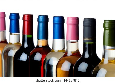 Different closed wine bottles in a row against white background