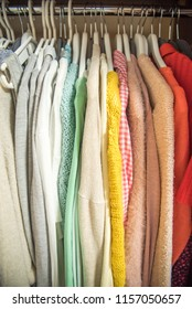 Different clothes on hangers close up. Multi-colored dresses and sweaters.