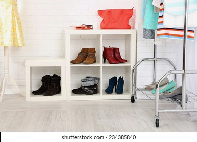 Different clothes on hangers, shoes on shelves in shop