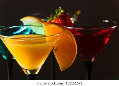 Different cocktails garnished with fruits , focus on foreground