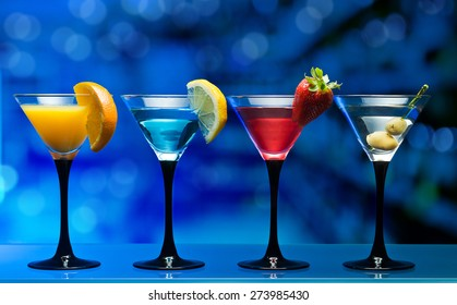 Different cocktails garnished with fruits on glass table in bar