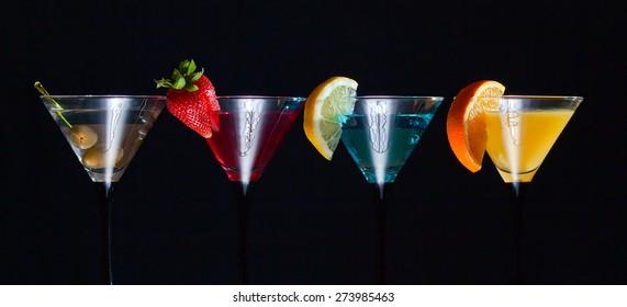 Different cocktails garnished with fruits on black background