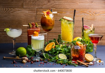 Different cocktails and ingredients for them on the background of boards