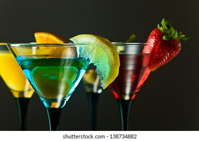 Different cocktails or longdrinks garnished with fruits