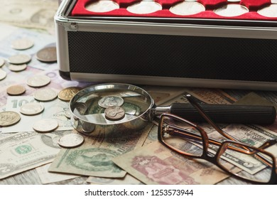Different collector's coins in the box with a magnifying glass, soft focus background