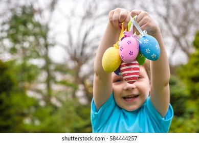 Different color Easter Eggs in a child's hands- egg hunt.