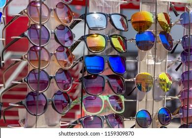 3c211bfa22d Different color glasses. Brilliant mirror multicolor sunglasses. A market  tray with multicolor sunglasses.