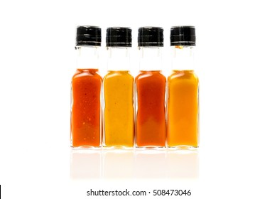 Different color home made hot sauce in glass bottles. Yellow, brown, mustard and red color chilly sauces made with bio eco ingredients. 100ml square bottles