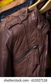 Different color leather jacket hanging on rack on blue background