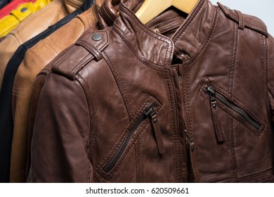 Different color leather jacket hanging on rack on white background
