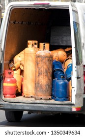 Different color and size cylinder gas bottles in a parked delivery van trunk for refill and supply