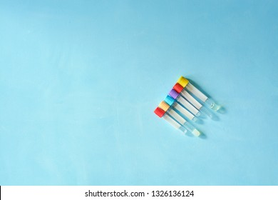 Different color and size empty vacuum venipuncture test tubes on blue background with copy space for text. Health life medicine concept.