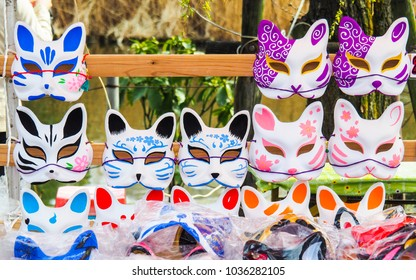 different color styles of Japanese traditional half face fox Kitsune masks hand painted for cosplay and costume hanging for sale