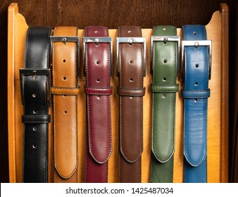 Different colored classic leather belts on display in luxury clothing boutique store.