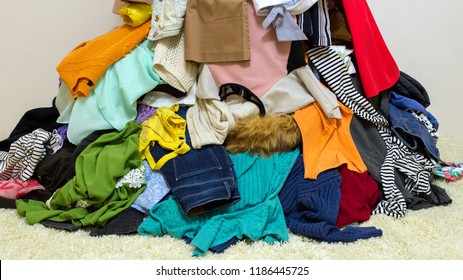 Different colored clothes background. Mixed up dresses, jeans, skirts and other used clothes