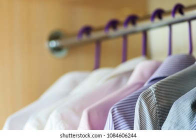 Different colored men's shirts hanging on hangers in wardrobe. Clothes in home closet close-up