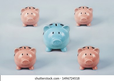 Different colored piggy bank standing out of the crowd. The uniqueness and leadership concept, individuality and difference. Finance and money saving process.