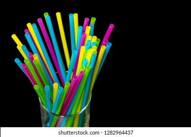 Different colored plastic drinking straws placed in a glass black background.jpg