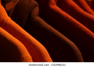 different colorful fleece jackets, colorful polar fleece jackets on a hanger macro shot made of recycled plastic bottles