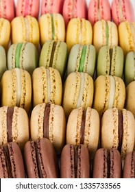 Different colorful french macaroons in a rows. Selective focus.