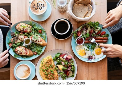 Different colorful meals for breakfast or lunch time on a plate with cutlery on woman's hands. Fried eggs, omelette, bruschetta and sausage on a wooden teble in restaurant. Flat lay top view. - Shutterstock ID 1567509190