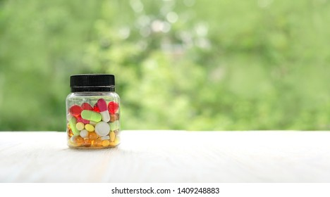 Different colorful medications pill in bottle close up. Many different drug and pill in Cup on blurred nature background. polypharmacy or multiple medication concept. banner, copy space