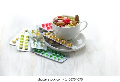 Different colorful medications pill close up. Many different drug and pill in Cup on white background. polypharmacy or multiple medication concept. Rational drug use concept. copy space