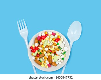 Different colorful medications pill. Many different drug and pill in plate, fork and spoon on blue background. polypharmacy or multiple medication concept. dieting concept. copy space