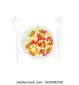 Different colorful medications pill. Many different drug and pill in plate, fork and spoon isolated on white background. polypharmacy or multiple medication concept. dieting concept. copy space