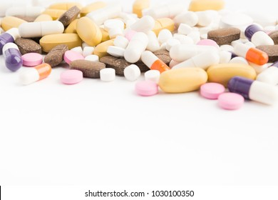 Different colorful pills on white table with copy space; selective focus